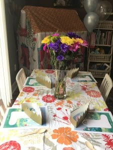 Wellie Wisher Birthday Party Table Decorations with flower tablecloth, fresh flowers and crowns